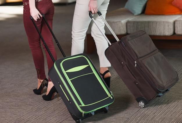 Reisendfrauenbeine, die mit einem koffer gehen