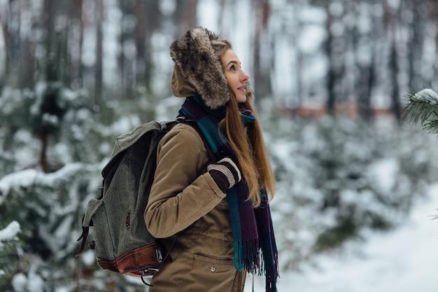 Reisendmädchen in der warmen winterjacke mit der pelzhaube und großem rucksack gehend in wald