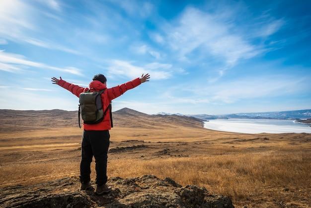 Reisendmann-abnutzungsrotkleidung und anheben des armes, der tagsüber auf berg im baikalsee, sibirien, russland steht.