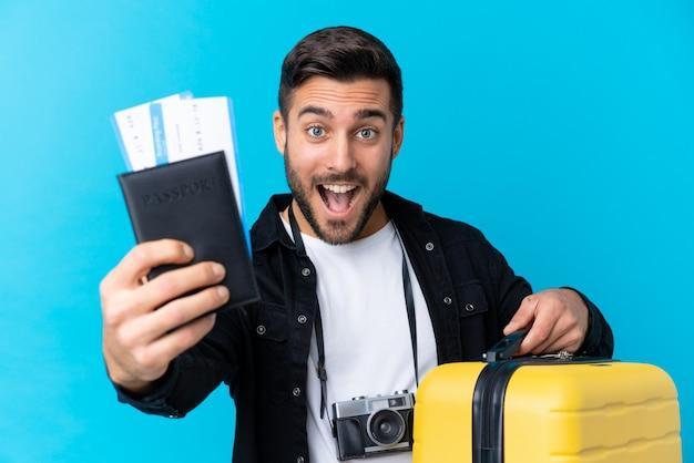 Reisendmann, der einen koffer und einen pass über lokalisierter blauer wand hält