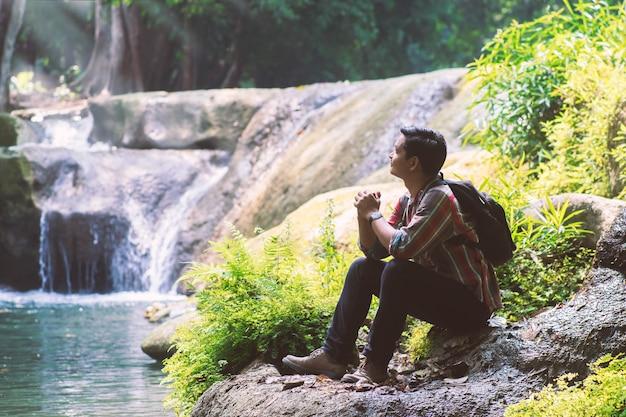 Reisendmann mit dem rucksack, der kamera mit grünem natürlichem hintergrund hält.