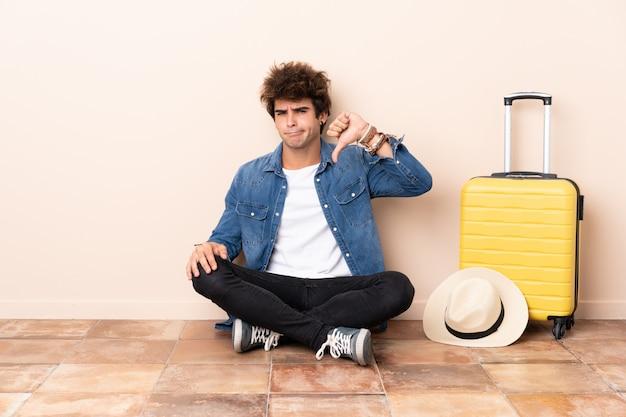 Reisendmann mit einem koffer, der auf dem boden sitzt