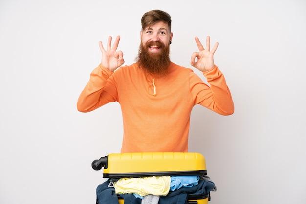 Reisendmann mit einem koffer voll von kleidung über der lokalisierten weißen wand, die ein okayzeichen mit den fingern zeigt