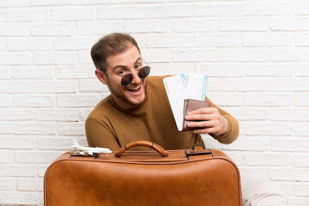 Reisendmann mit koffer und bordkarte und halten eines spielzeugflugzeuges