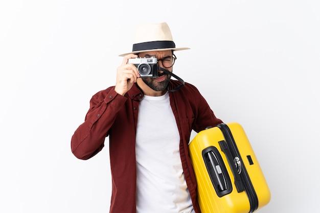 Reisendmannmann mit dem bart, der einen koffer über weiß hält