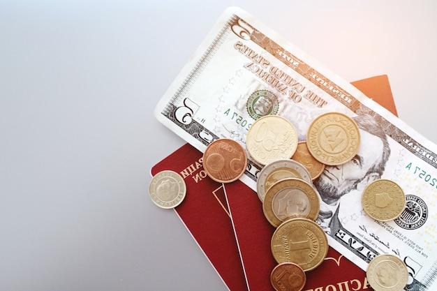 Reisepass mit banknoten und münzen auf einer ebene.