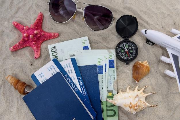 Reisepass mit euro und spielzeugflugzeug auf sand