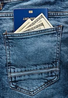 Reisepass mit hundert-dollar-scheinen in der gesäßtasche der blue jeans. reisekonzept oder einwanderung.