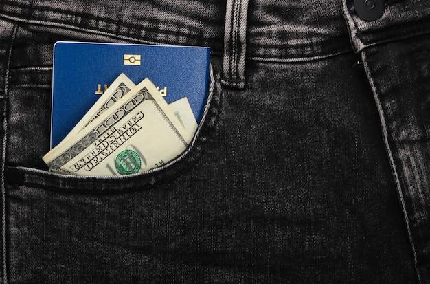 Reisepass mit hundert-dollar-scheinen in der vordertasche grauer jeans. reisekonzept oder einwanderung.