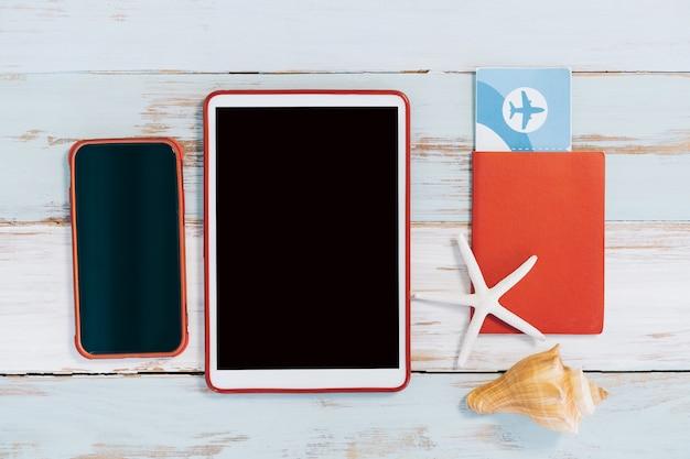 Reisepass mit ticket und telefon und tablet auf einem holztisch