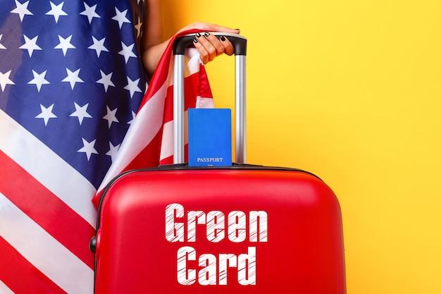 Reisepass mit usa-flagge auf rotem koffer, grünes kartenkonzept