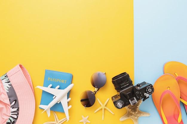 Reisepass, spielzeugflugzeug, kamera und freizeitzubehör auf farbigem hintergrund mit kopierraum