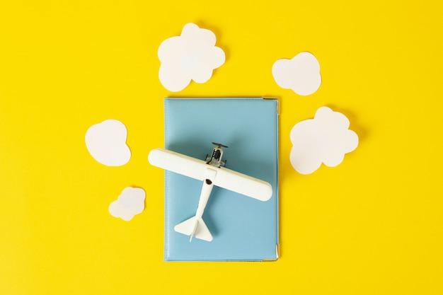 Reisepass, spielzeugflugzeug und dekorative wolken auf gelb