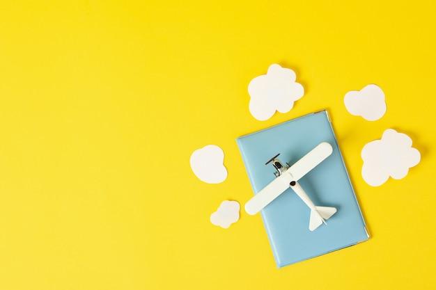 Reisepass, spielzeugflugzeug und dekorative wolken auf gelber draufsicht