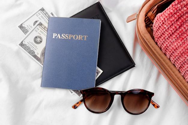 Reisepass und banknote neben dem gepäck