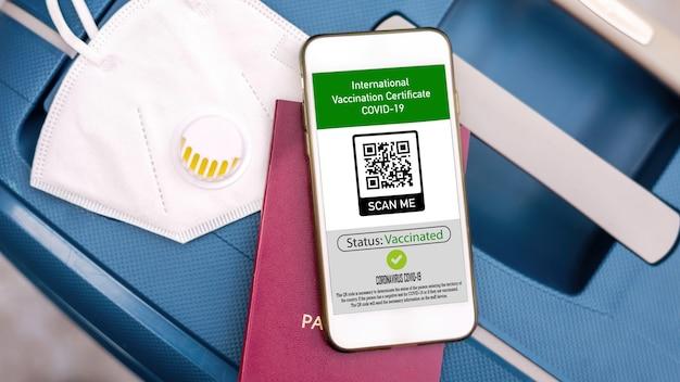 Reisepass und smartphone mit internationalem impfausweis covid-19 qr-code auf koffer mit maske