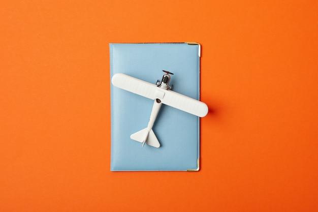 Reisepass und spielzeugflugzeug auf orange