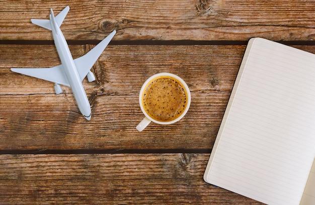 Reiseplan flugzeug papiernotiz in kaffeetasse