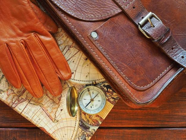 Reiseplanung alte kompasskarte leder aktentasche und handschuhe auf holzuntergrund