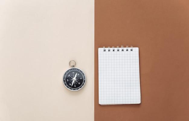 Reiseplanung oder abenteuer. kompass mit einem notizbuch auf einem beige-braunen hintergrund. ansicht von oben