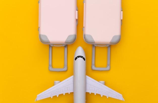 Reiseplanung. reisegepäck mit zwei spielzeugen und flugzeug auf gelb. flach legen