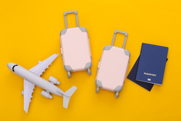 Reiseplanung. reisegepäck und reisepass mit zwei spielzeugen, flugzeug auf gelb. flach legen