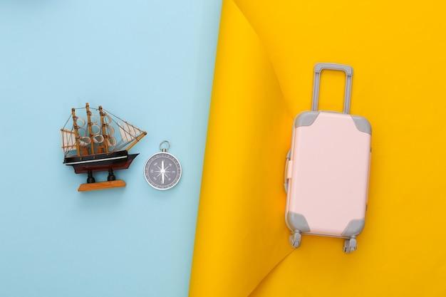 Reiseplanung. spielzeugreisegepäck, schiff und kompass auf gelbem blauem papier. flach legen