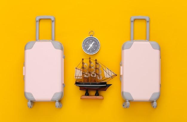 Reiseplanung. spielzeugreisegepäck, schiff und kompass auf gelbem papier. flach legen