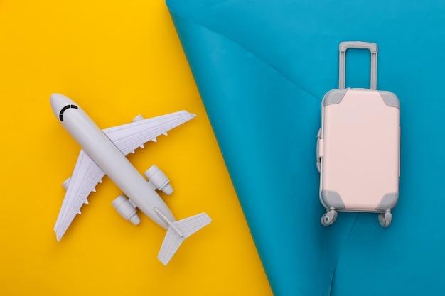 Reiseplanung. spielzeugreisegepäck und -flugzeug auf blauem gelb. flach liegen.