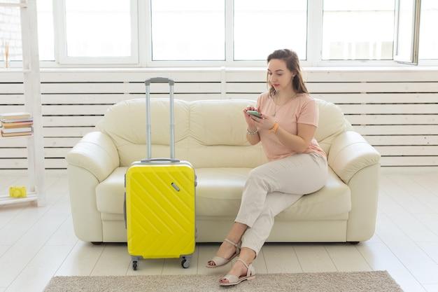 Reisereise- und urlaubskonzeptfrau mit gelbem koffer wartet auf das taxi