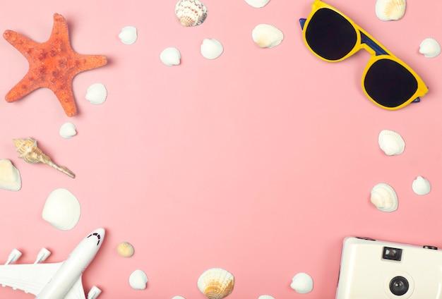 Reisesommerhintergrundsonnenbrillenkameraflugzeug und strandzubehör auf einem farbigen rosa hinterg...