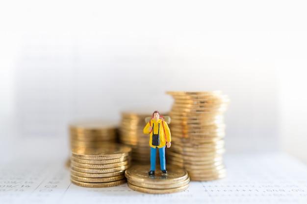 Reisespar- und planungskonzept. reisende miniaturmenschenfigur mit rucksack stehend auf stapel von goldmünzen auf banksparbuch mit kopienraum.