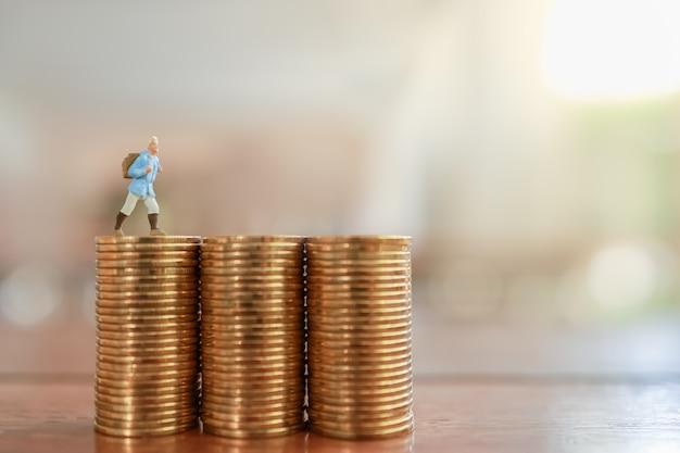 Reisespar- und planungskonzept. reisende miniaturmenschenfigur mit rucksack stehend auf stapel von goldmünzen auf holztisch mit kopienraum.