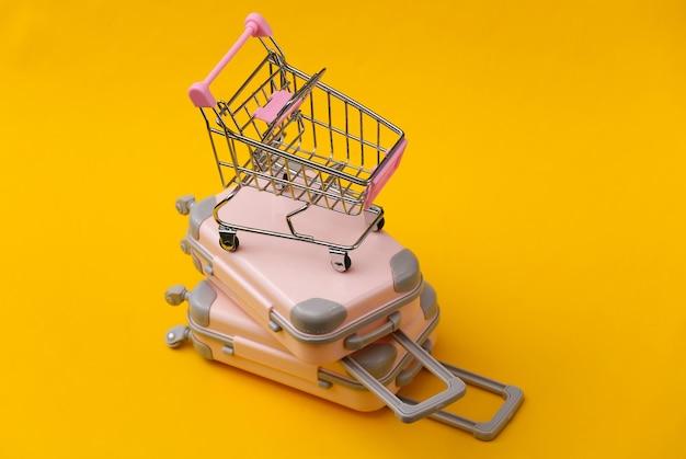 Reisestillleben, urlaub oder tourismuskonzept. zwei mini-reisegepäckkoffer und einkaufswagen auf gelb