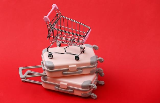 Reisestillleben, urlaub oder tourismuskonzept. zwei mini-reisegepäckkoffer und einkaufswagen auf rot