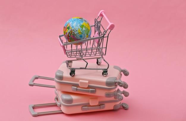 Reisestillleben, urlaub oder tourismuskonzept. zwei mini-reisegepäckkoffer und einkaufswagen mit globus auf rosa
