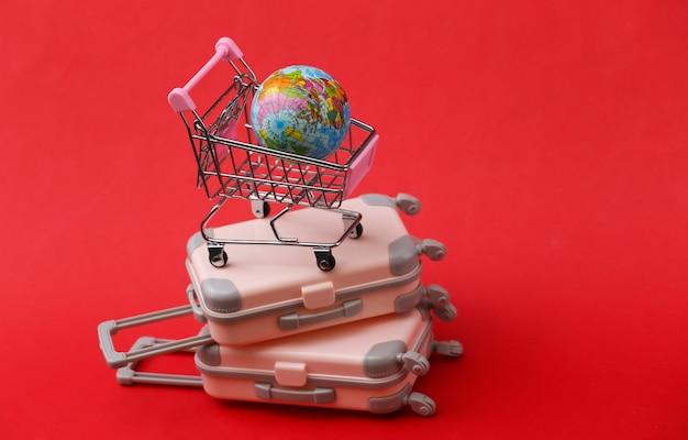 Reisestillleben, urlaub oder tourismuskonzept. zwei mini-reisegepäckkoffer und einkaufswagen mit globus auf rot