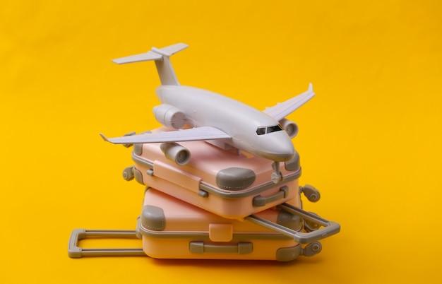 Reisestillleben, urlaub oder tourismuskonzept. zwei mini-reisegepäckkoffer und flugzeug auf gelb