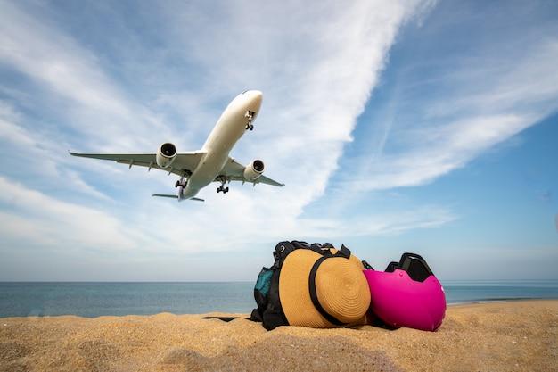 Reisetasche am strand und flugzeuglandung