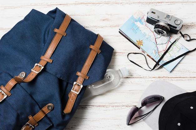 Reisetasche und zubehör auf hölzernem hintergrund