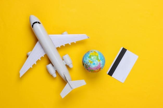 Reisethema. flugzeug mit einem globus, kreditkarte auf einer gelben oberfläche. draufsicht, flach liegen