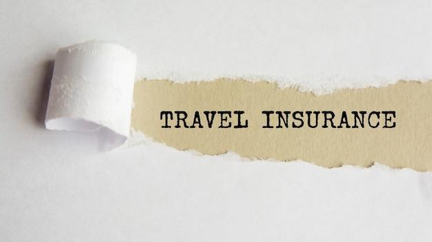 Reiseversicherung. wörter. text auf grauem papier auf zerrissenem papierhintergrund.