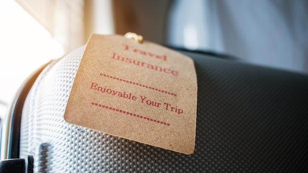 Reiseversicherungsetikett auf koffersicherheit mit den buchstaben, die ihre reise auf taschenlicht unscharfer hintergrund genießen, die beabsichtigt ist, deckt medizinische ausgaben, reiseabbruch oder flugunfall ab.