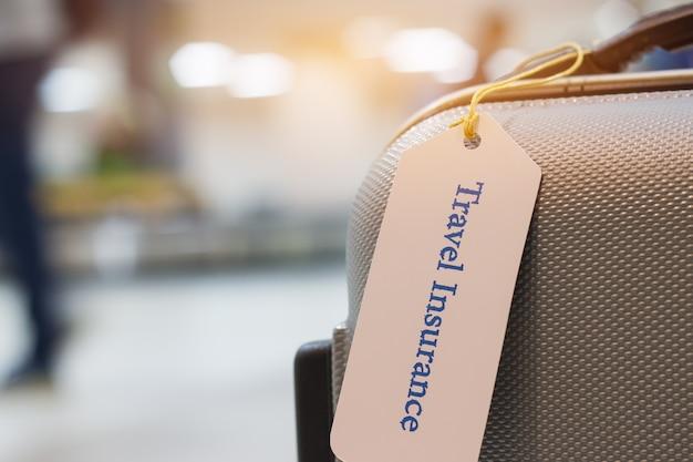 Reiseversicherungstag auf kofferhalter mit dem tag gebunden