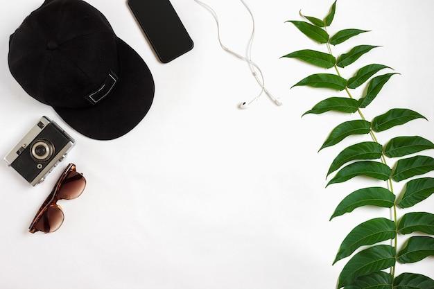 Reisezubehör auf weißem hintergrund smart headphones cap kamera und sonnenbrille top view point