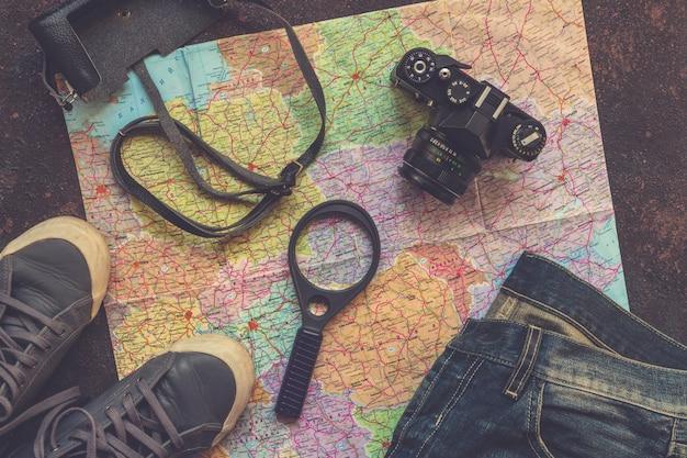 Reisezubehörkamera, strohhut, karte, schuhe, laptop, auf einem draufsichtplan des dunklen hintergrundes flach