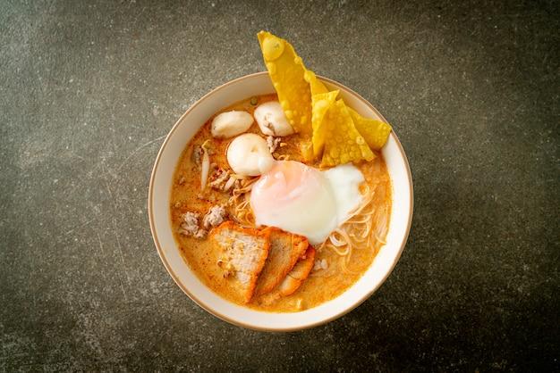 Reisfadennudeln mit fleischbällchen, gebratenem schweinefleisch und ei in pikanter suppe - tom yum noodles