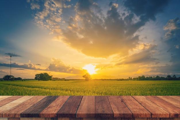 Reisfeld sonnenuntergang und leerer holztisch für produktanzeige und montage.