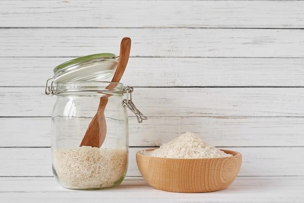 Reiskörner in der hölzernen schüssel und im glasgefäß