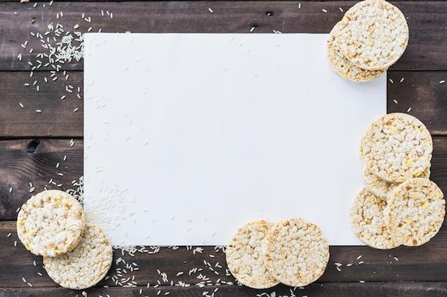 Reiskörner und luftgestoßener reiskuchen auf weißem leerem papier über dem hölzernen schreibtisch